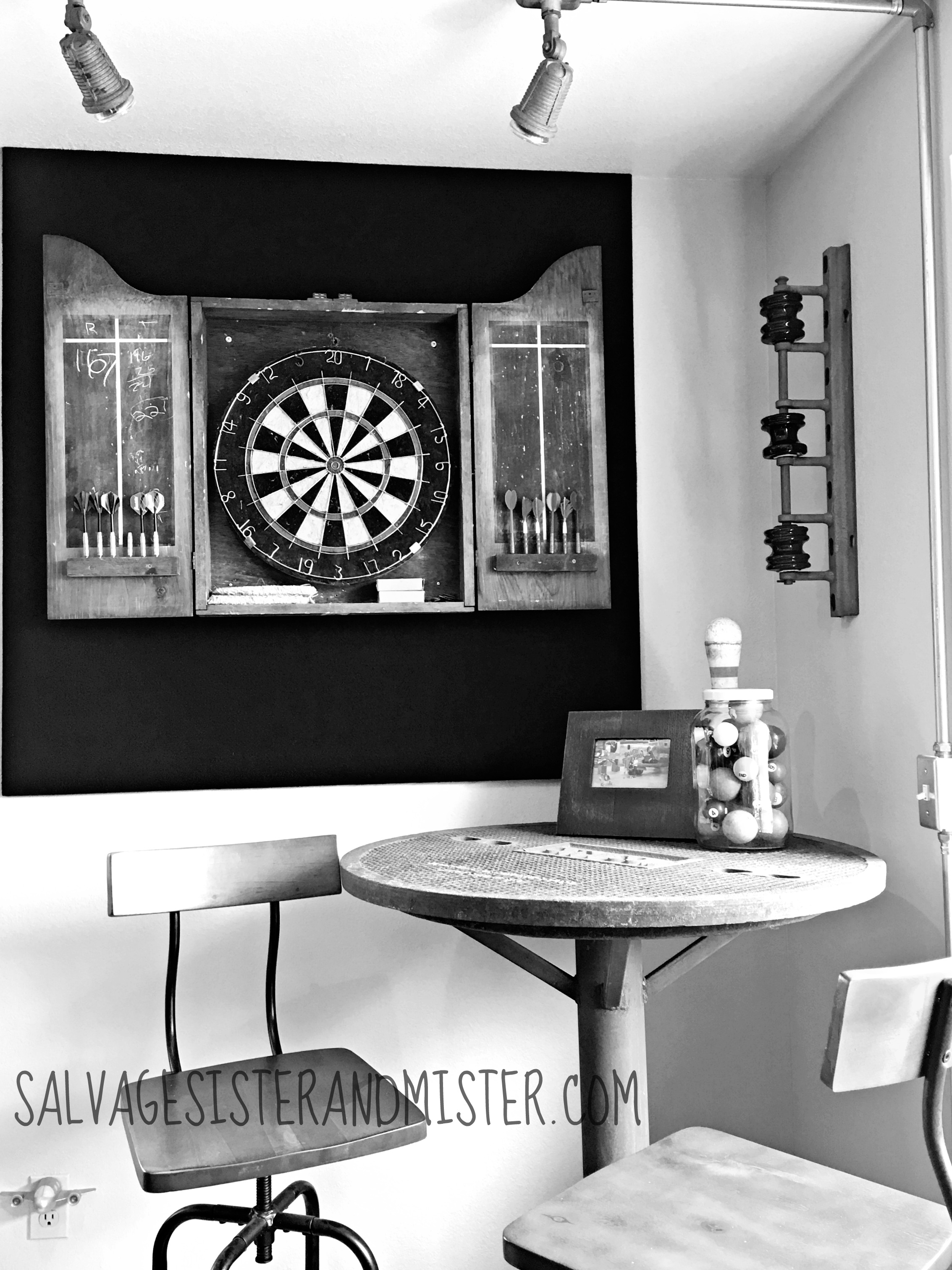 We are participating in the One Room Challenge- to makeover a room in 7 weeks. We have a room above our garage that has been a catch all. We are doing a budget friendly makeover to this part of our home. For our third week we are showing this industrial bar table, dart board, and light area that we have added. Perfect for a man cave. Junk decor galore.