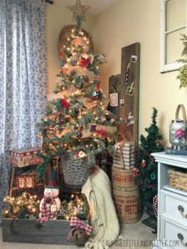 Discount tree turned into a pretty tree. Decorating for the holidays using what you have, flea market finds, junkin decor. This antique olive bucket and a vintage chair brings the height the tree needs. Added some extra items to the bottom to finish the space. Holiday decorating.