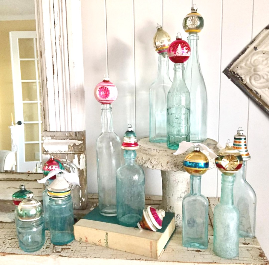 Need Christmas decor quick and on a budget? How about some vintage bottles with ornaments on top? Simple farmhouse style Christmas. Come see all the upcycle Chrismtas ideas to be inspired to make the most with whatever it is you have.