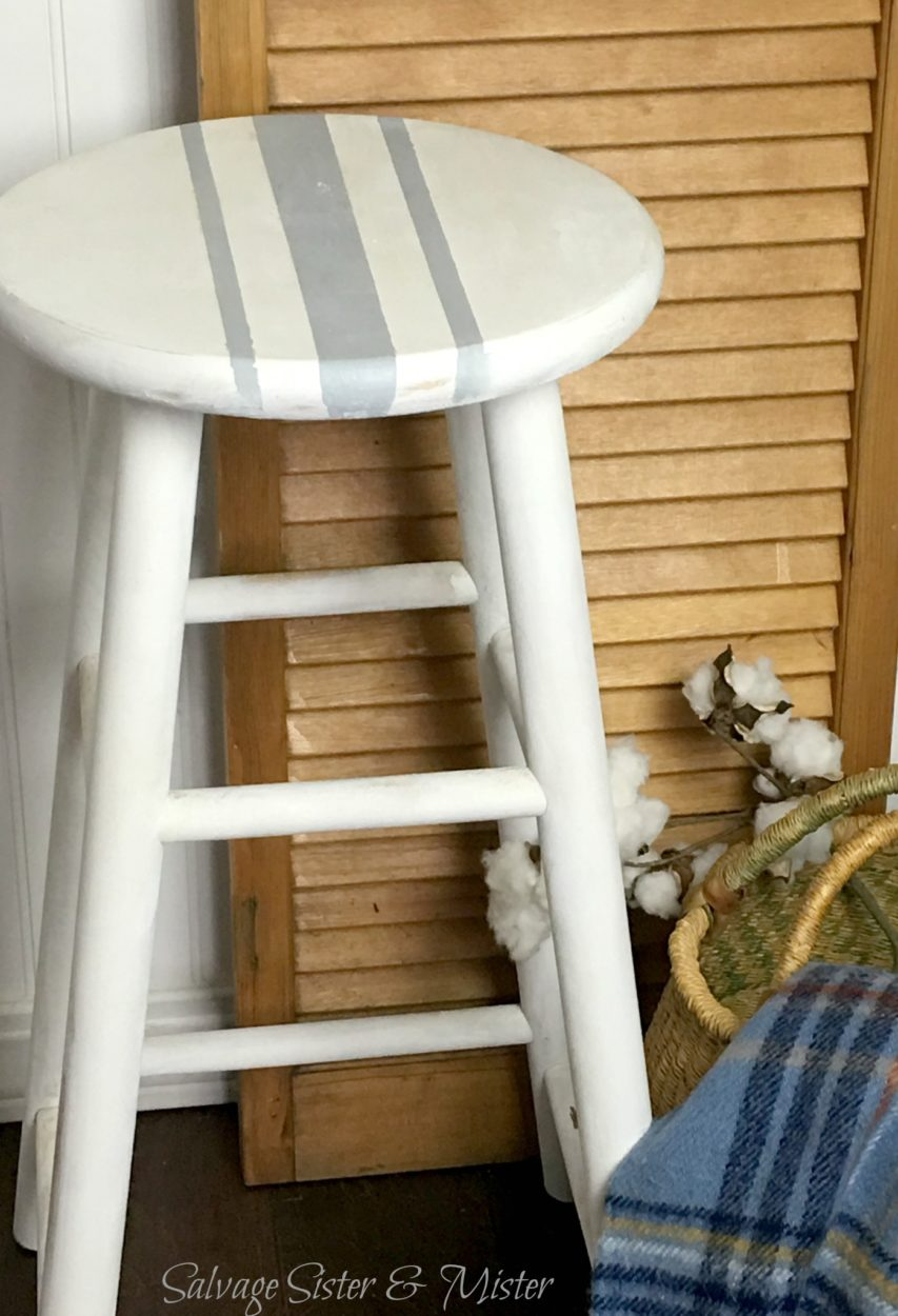 Plain thrifted barstool is turned into a DIY farmhouse barstool with just a little paint. It has a whole new look now. This fixer upper style stool will fit in any farmhouse style home. Grain sack pattern on top.