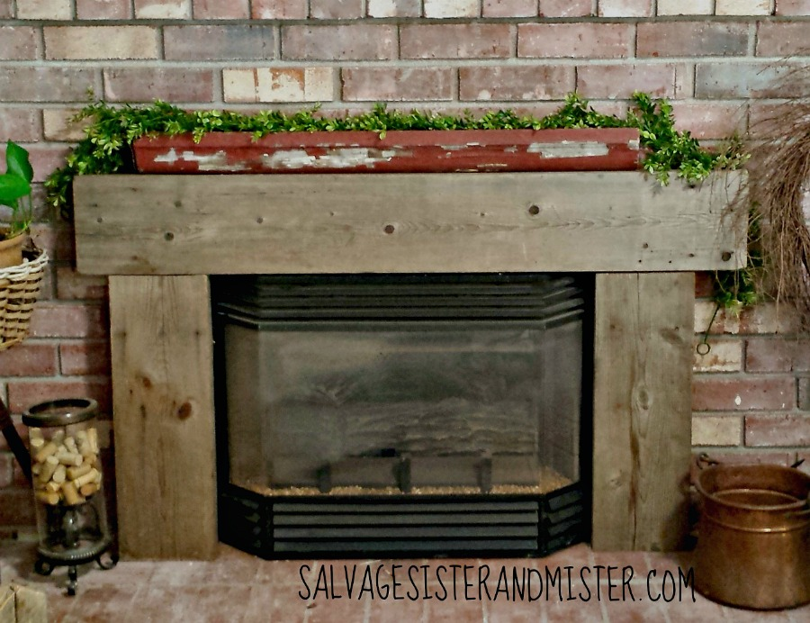 Covering up a gas insert fireplace with some salvaged wood.