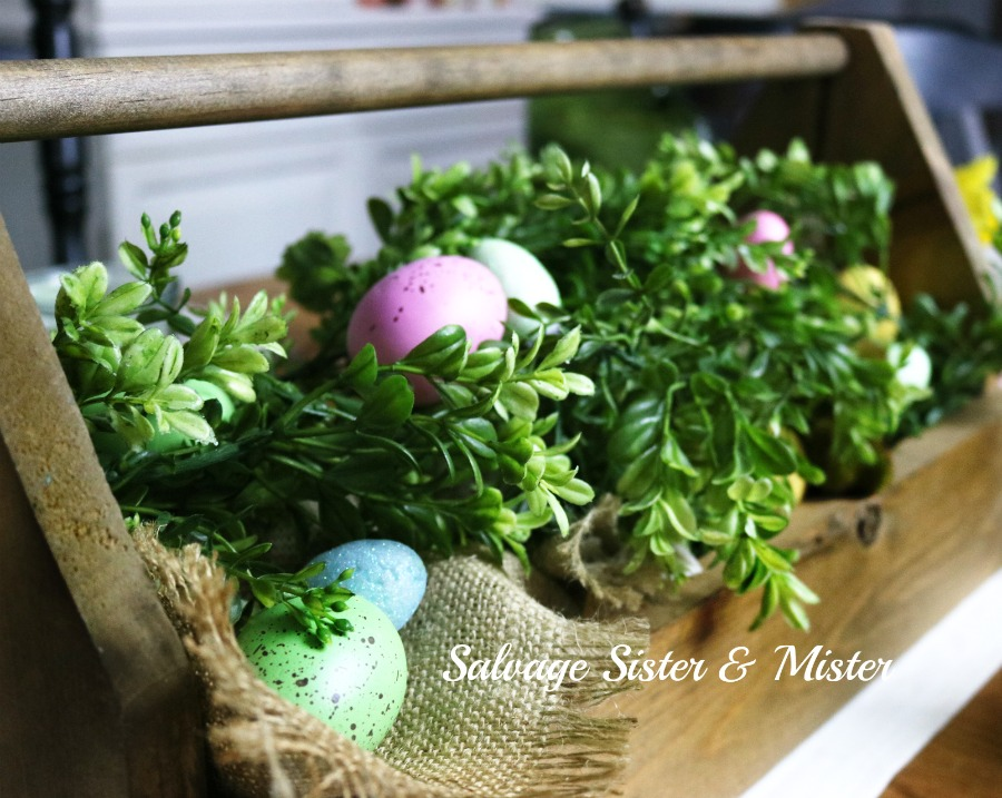 Spring table setting centerpiece. This wood tool box was made at a hardware store build. I can change it out for whatever holiday decor I want. This is my Easter or spring farmhouse look centerpiece. Used some green garland and easter eggs I already had.