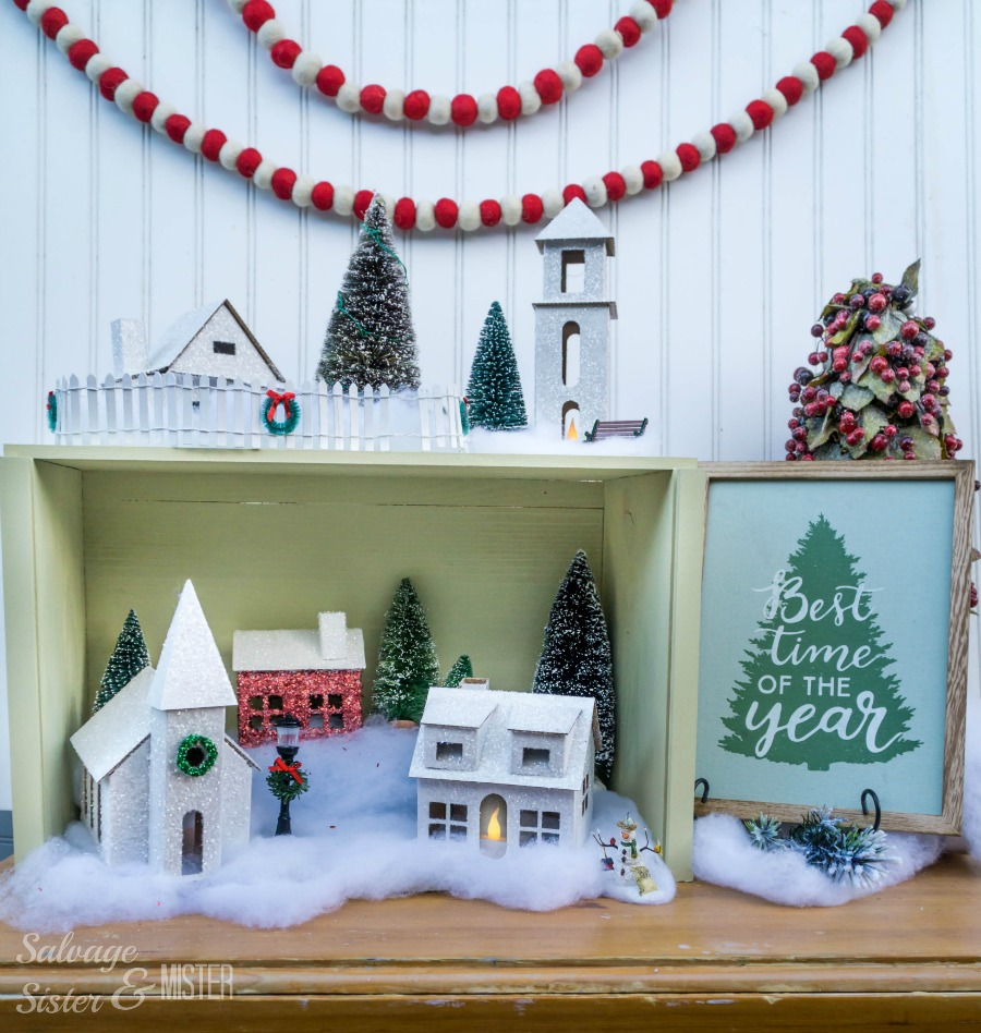 DIY Christmas village in a box. Easy to store and budget friendly holiday decor. Customize your way. Use cardboard bozes, thrifted items, or these pre pressed boxes. When you are done, box it up and place it in storage. Great for small space decorating.