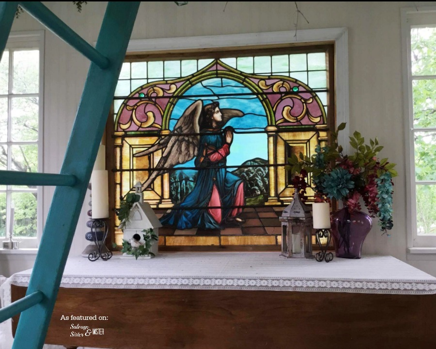 Stained glass angel window built for this cottage made of repurposed materials. Also, see a cintage truck water feature in this backyard oasis