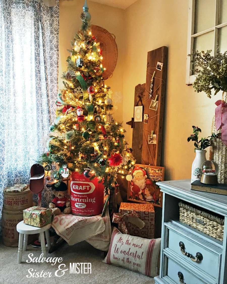 Our simple vintage Christmas tree is inexpensive and filled with thrifted and DIY items. This display also inlcudes a retro santa print, a toy,and the DIY north pole mailbox.