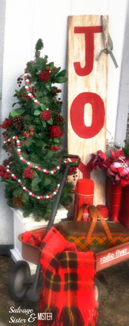 Vintage inspired holiday porch using thrifted items, things on hand, and DIy projects. Holiday decor doesn't have to be expensive. Raidof floyer, thermoses, vintagepicnic tin, plaid blanket, rain boots, etc to make a Christmas porch decor.