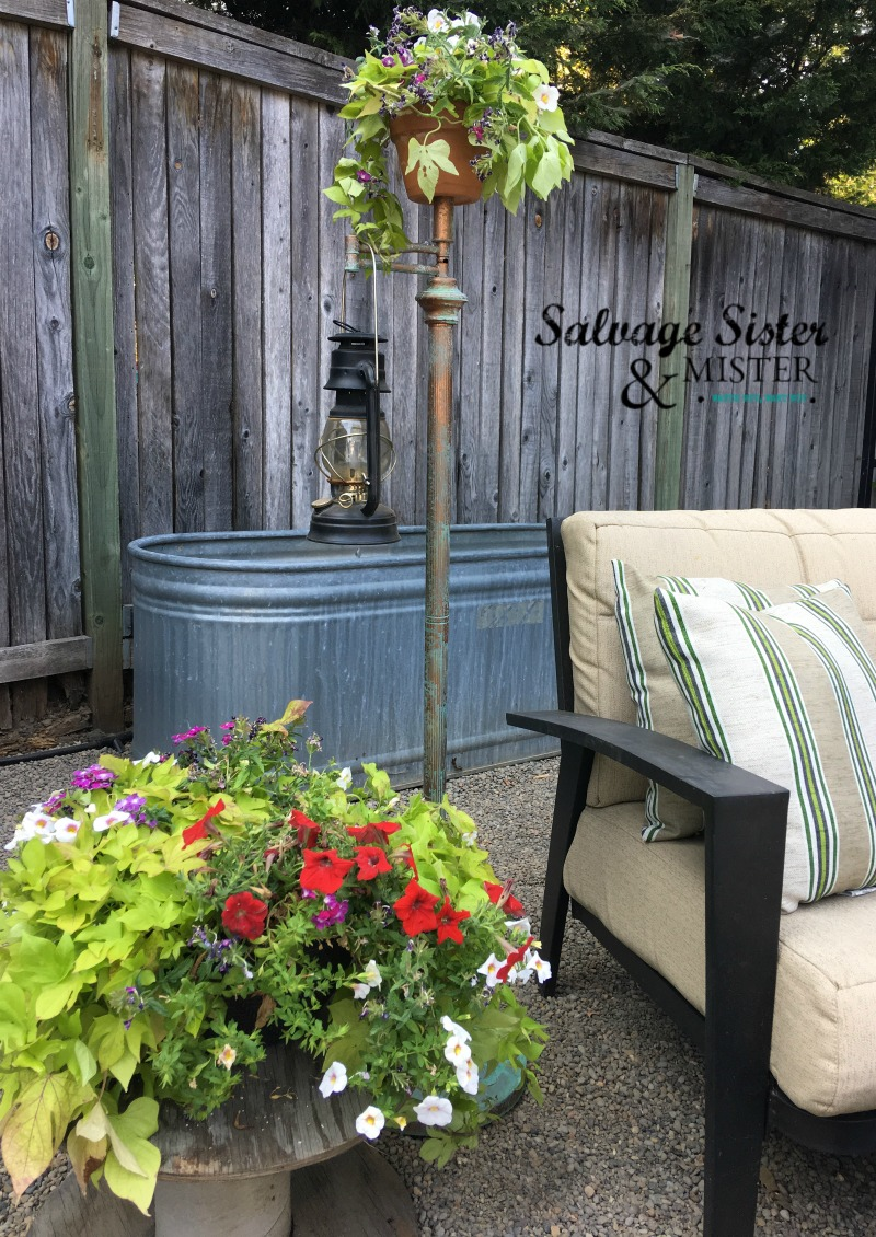 From a free pile this arm lamp was rescued and given a new purpose (repurpose).  DIY project - Upcycled Lantern Stand with patina is an easy project and makes a great backyard item on a budget. #repurpose #upcycled #backyard #junkin found on salvagesisterandmister.com