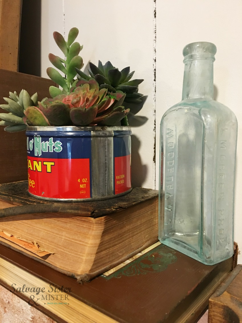 antique nut can, vintage aque glass bottle, and old books are thrifted finds used to make this vintage mantel decor area