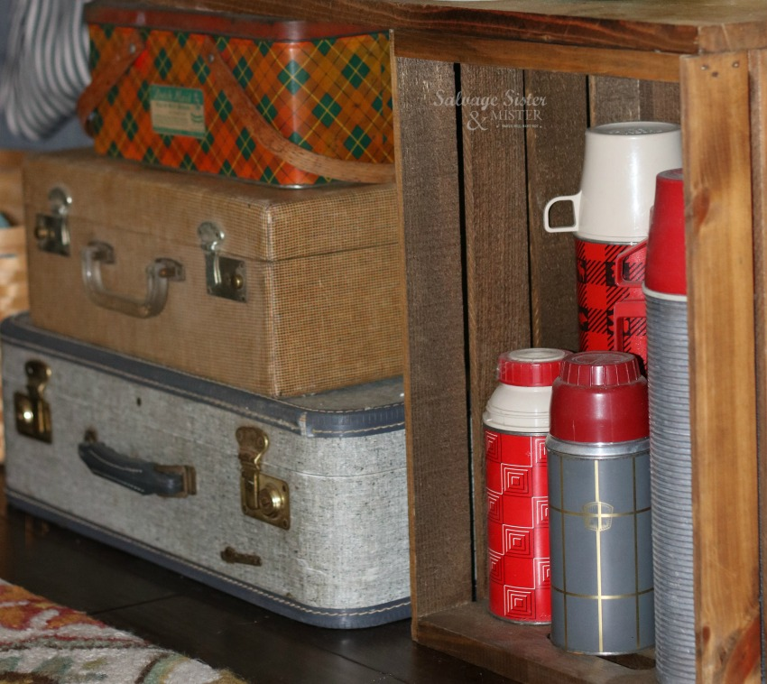 Using a wood plank, crates, and some thrift decor items for a behind the couch table on salvagesisternandmister.com