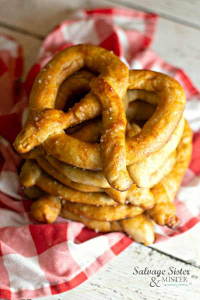 Oh yum! Here is a Amish style buttery homemade soft pretzel recipe for anytime of the year (Octoberfest, National Pretzel Day, or anytime). Learn about the legend of the pretzel and how fun it is to make with kids. These tasty bread treats are great with dipping sauces or make them sweet with a cinnamon and sugar dusting. Get this recipe on salvagesisterandmsiter.com